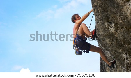 Young male climbing on a cliff on blue cloudy sky background - stock photo