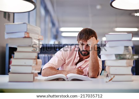 Young male college student sitting at the library desk with two big pile of books, bored and tired to study high school student boy reading the book, preparing to the exams in library - stock photo