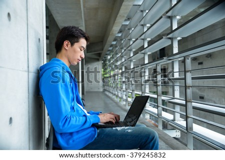 Young male college student sitting use laptop at campus
