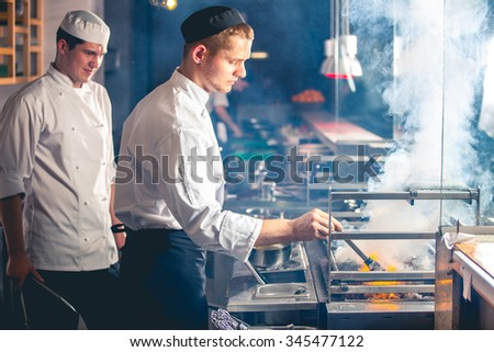 young male cooks preparing meal on the grill - stock photo