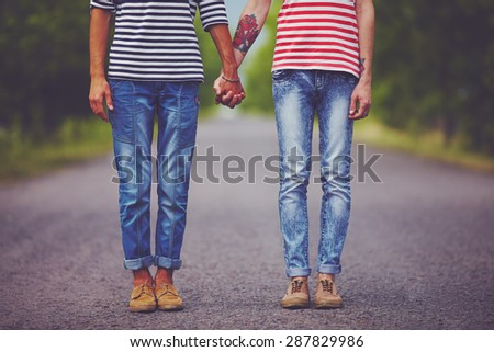 young male couple holding hands standing on their way together - stock photo