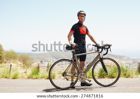 Young male cyclist standing with his bike while out for a ride in countryside. Young athletic man taking a break after a good workout. - stock photo
