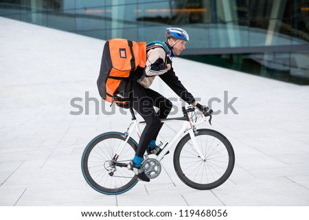 Young male cyclist with courier delivery bag riding bicycle - stock photo