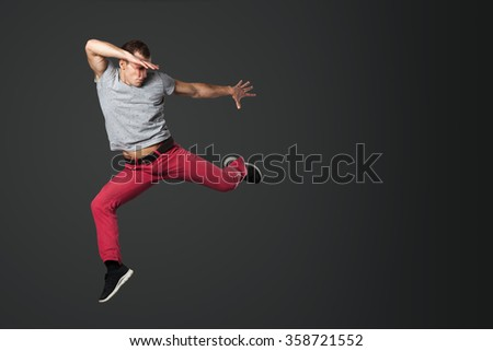 Young male dancer jumping isolated on gray background. - stock photo