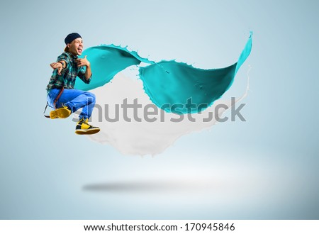 young male dancer jumping surrounded by splashes of paint