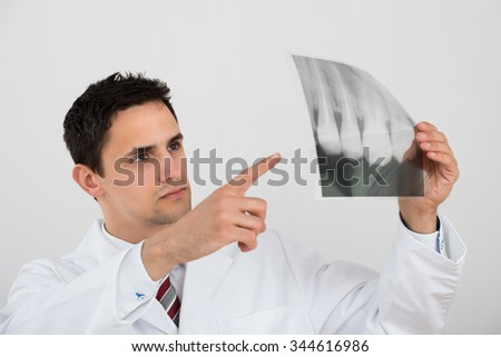 Young male dentist examining dental xray against white background - stock photo