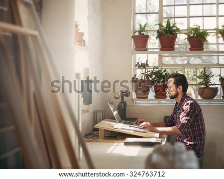 Young male designer sitting and working on his laptop in an office space in his creative design studio - stock photo