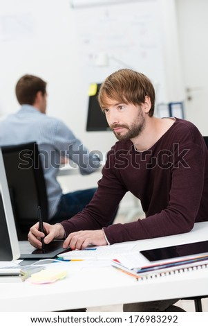 Young male designer working at his desktop computer using a tablet and stylus as he watches his monitor