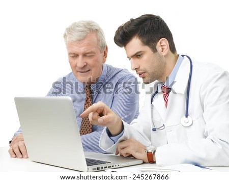 Young male doctor analyzing the result of the test on computer with old male patient. Isolated on white.  - stock photo