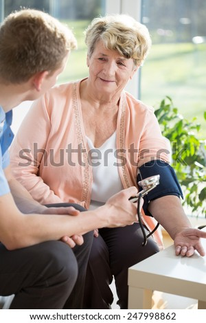 Young male doctor checking woman's blood pressure