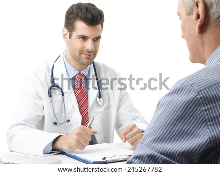 Young male doctor discussing with old male patient while sitting against white background.  - stock photo