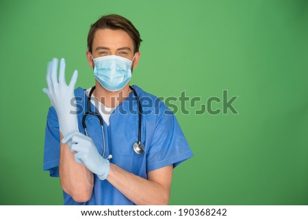 Young male doctor wearing a mask, gown and stethoscope putting on surgical gloves on a green background with copyspace - stock photo