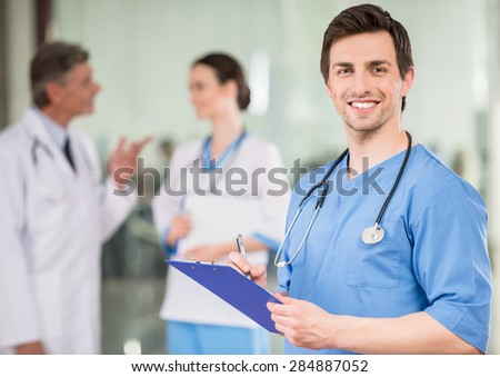 Young male doctor with colleagues at doctor's office. - stock photo