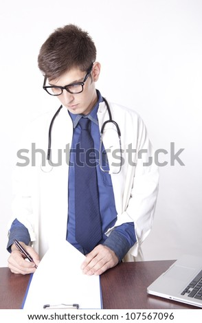 Young male doctor writing.