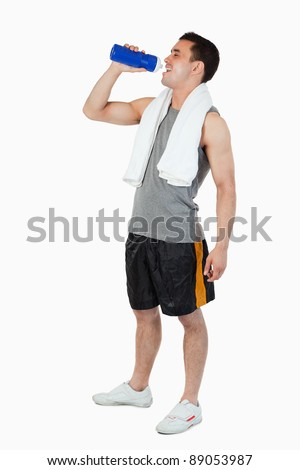 Young male drinking after workout against a white background - stock photo