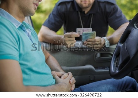 Young male driver stopped for policeman's control - stock photo