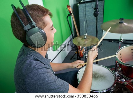 Young male drummer wearing headphones while performing in recording studio - stock photo