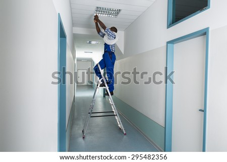 Young Male Electrician On Stepladder Installing Light On Ceiling