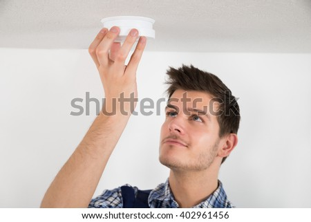 Young Male Electrician Testing Smoke Detector At Home