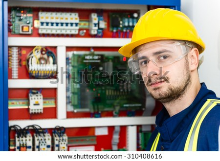 Young male electrician trying to solve the problem. Selective focus. - stock photo