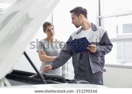 Young male engineer explaining car engine to female customer in workshop - stock photo