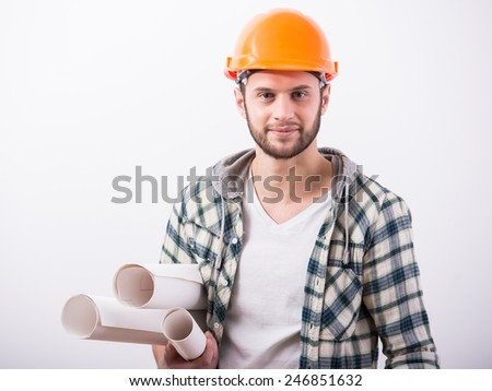 Young male engineer with helmet is holding blueprints, on grey background. - stock photo