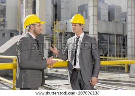 Young male engineers discussing at construction site - stock photo