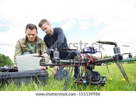 Young male engineers using laptop by UAV octocopter in park - stock photo
