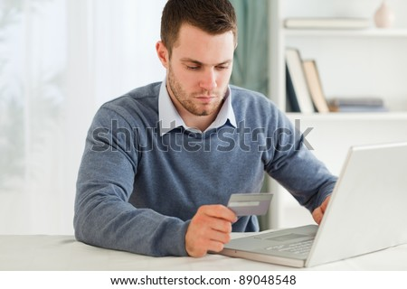 Young male entering credit card information in his notebook - stock photo