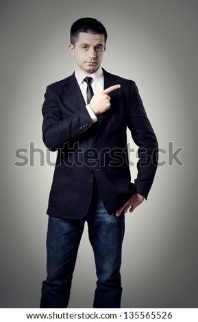 young male entrepreneur pointing at something interesting against  on a gray background