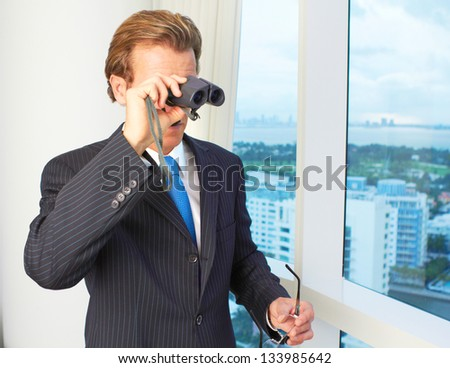 Young male executive in business suit looking through binoculars. Horizontal shot.