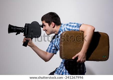 Young male filmmaker with old movie camera and a suitcase in his hand. Traveler with a camera - stock photo
