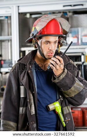 Young male firefighter conversing on walkie talkie at fire station - stock photo