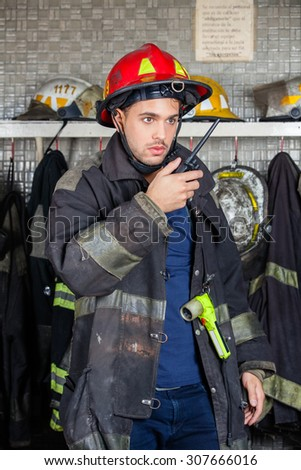 Young male firefighter looking away while using walkie talkie at fire station - stock photo
