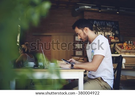 Young male freelancer chatting on mobile phone while sitting front open laptop computer in natural food cafe, handsome man reading text message during work on net-book in comfortable coffee shop - stock photo