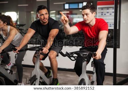 Young male friends doing some spinning on a bicycle at a gym and talking during the workout - stock photo