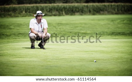 Young male golf player with putter squatting to study the green at golf course. - stock photo