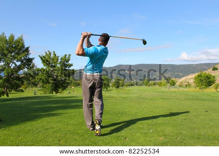Young male golfer hitting a driver from the tee-box - stock photo