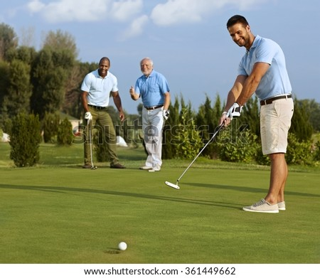 Young male golfer putting ball on green in the hole.