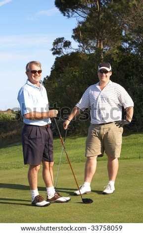 Young male golfer with his senior father ready to tee off on a beautiful summer day - stock photo
