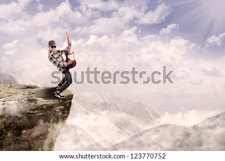 Young male guitarist is playing outdoor on top of a mountain - stock photo