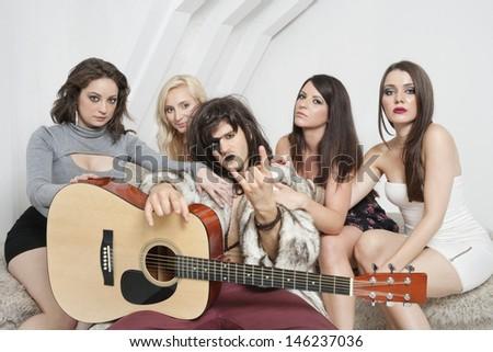 Young male guitarist with cool gesture surrounded by female friends - stock photo