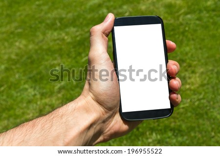 Young male hand holding and showing smart phone with blank white screen on green background filled grass. - stock photo