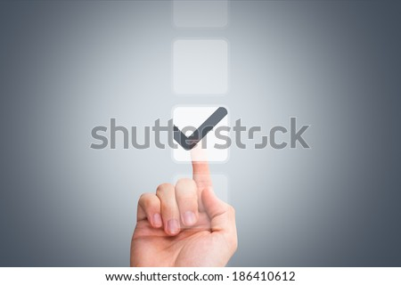 Young male hand touching, pressing modern button and ticking check box out of empty boxes on digital screen interface on virtual background. - stock photo