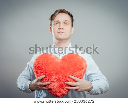Young male holding a red heart shaped pillow  - stock photo