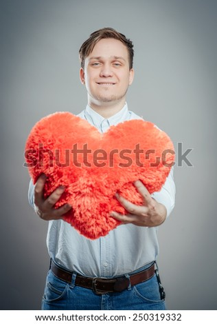 Young male holding a red heart shaped pillow and  - stock photo