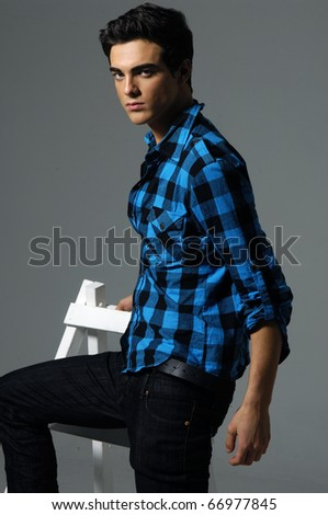 young male in shirt on grey background - stock photo