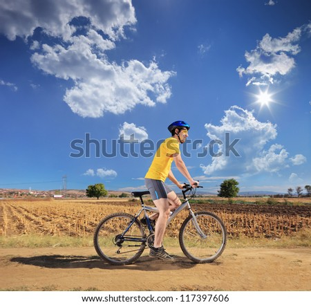 Young male in yellow shirt riding a bike on a sunny day in Macedonia - stock photo