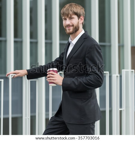 Young male is posing with cup of coffee in hand - stock photo