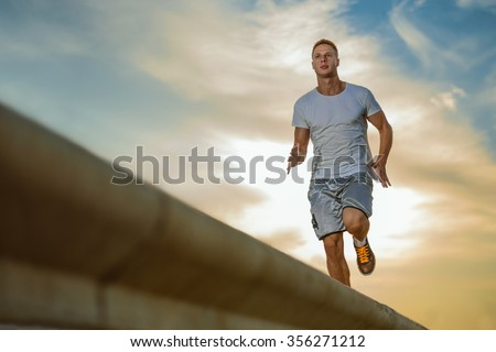 Young male jogger athlete training and doing workout outdoors in city - stock photo
